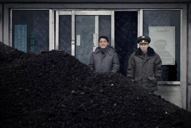 Sĩ quan quân sự Triều Tiên đứng cạnh nơi tập kết than trên bờ sông Áp Lục gần biên giới Triều Tiên - Trung Quốc (Ảnh: AFP)