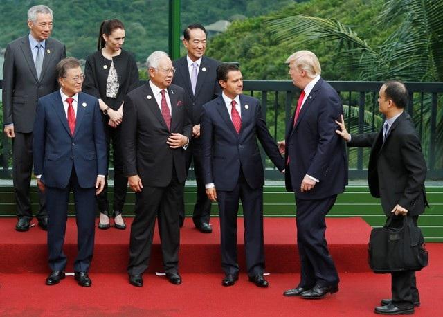 Tổng thống Trump tiến tới vị trí chụp ảnh cùng các lãnh đạo của 21 nền kinh tế thành viên APEC. Thứ tự hàng dưới từ trái qua gồm: Tổng thống Hàn Quốc Moon Jae-in, Thủ tướng Malaysia Najib Razak, Tổng thống Mexico Enrique Pena Nieto. Thứ tự hàng trên từ trái qua gồm: Thủ tướng Singapore Lý Hiển Long, Thủ tướng New Zealand Jacinda Ardern và đại diện của Đài Bắc (Trung Hoa) James Soong. (Ảnh: Reuters)