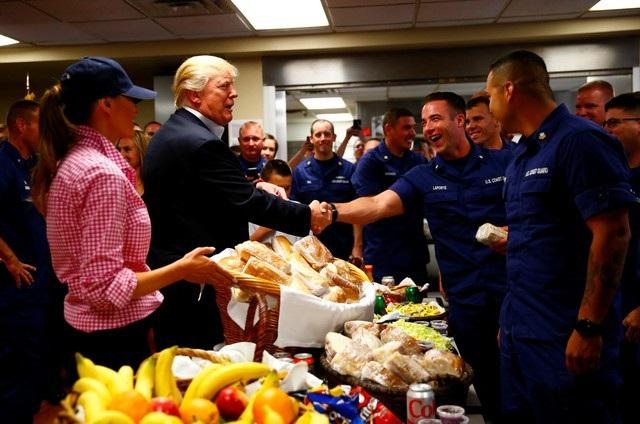 """Tổng thống Trump bắt tay và cảm ơn từng thành viên của Lực lượng Tuần duyên tại căn cứ ở Florida. Ông chủ Nhà Trắng cũng khen họ giữ được """"thể trạng tốt"""" và còn nói đùa rằng ông muốn vật tay với họ. (Ảnh: Reuters)"""