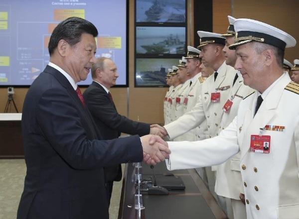 Chủ tịch Trung Quốc Tập Cận Bình và Tổng thống Nga Vladimir Putin bắt tay các tướng lĩnh tham dự cuộc tập trận chung giữa hai nước tại cảng không quân Wusong, Thượng Hải, Trung Quốc ngày 20/5/2014. (Ảnh: Tân Hoa Xã)