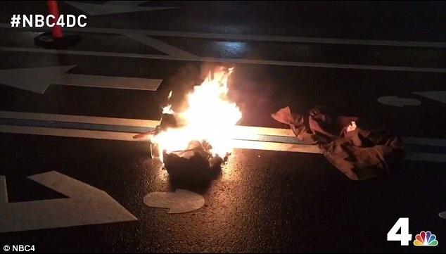 Người đàn ông phản đối ông Trump đã đốt quần áo ở ngay bên ngoài khách sạn Trump International tại Washington (Ảnh: NBC)
