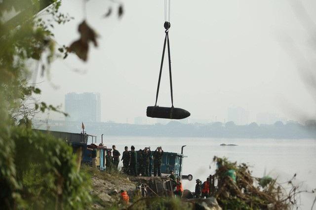 Ngày 28/11, lực lượng người nhái (thợ lặn) lặn xuống sông Hồng ở khu vực cầu Long Biên (Hà Nội) móc dây vào quả bom nằm ở độ sâu khoảng 6m tính từ mặt nước. Sau đó quả bom được kéo lên gần mặt nước, được lai dắt về vị trí tập kết với sự hỗ trợ của người nhái. (Ảnh: Toàn Vũ)
