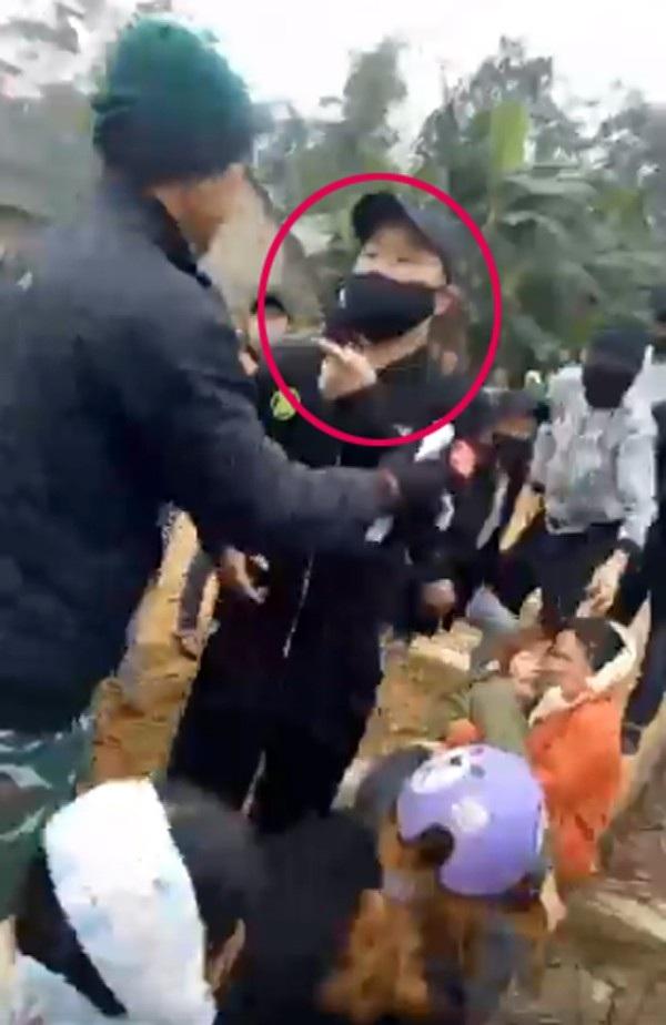 Một thanh niên bịt mặt chỉ tay đe dọa người dân (ảnh cắt từ clip)