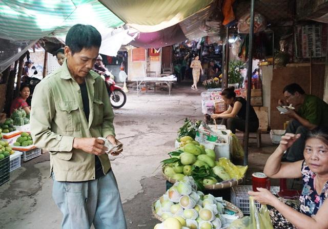 Ông Nguyễn Văn Hảo đi thu tiền công ở các chủ hàng hoa quả trong chợ. Mỗi chuyến hàng ông được trả từ 2-5 nghìn đồng tùy khoảng cách chuyên chở...