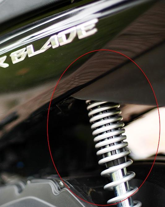 Chi tiết bằng nhựa màu đen ngăn cách lò xo giảm xóc và ty giảm chấn trên một mẫu xe ga khác tại Việt Nam