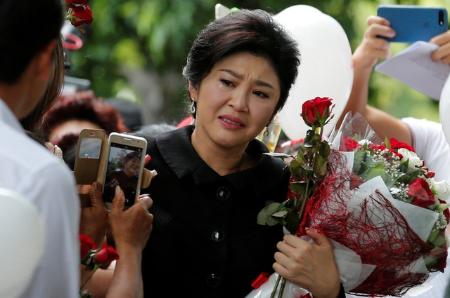 Cựu thủ tướng Thái Lan Yingluck Shinawatra khóc khi nhận hoa của những người ủng hộ ngoài tòa án (Ảnh: Reuters)