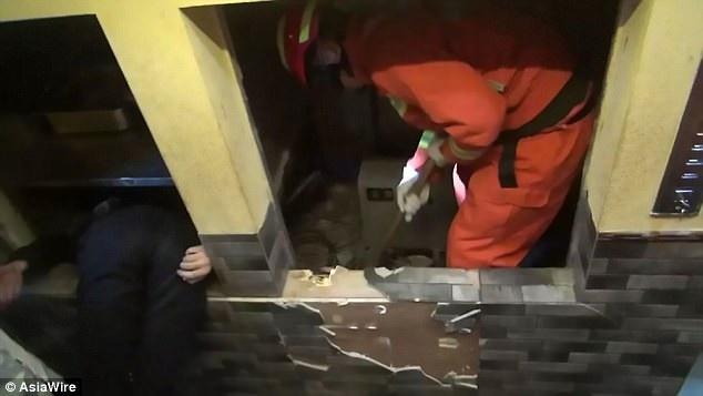 Lực lượng cứu hỏa nỗ lực giải cứu thanh niên xấu số khỏi thang máy chở đồ ăn. (Ảnh: Asiawire)