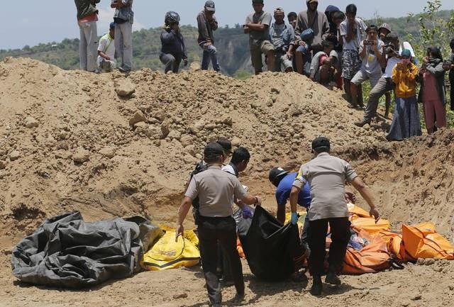 Đội cứu hộ đưa thi thể các nạn nhân tới nơi chôn cất tập thể. (Ảnh: AFP)