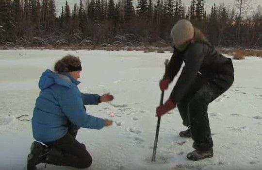 Một nhà khoa học đục một hố giữa hồ băng giá, một người khác cầm một que diêm ngồi cạnh - ảnh cắt từ clip