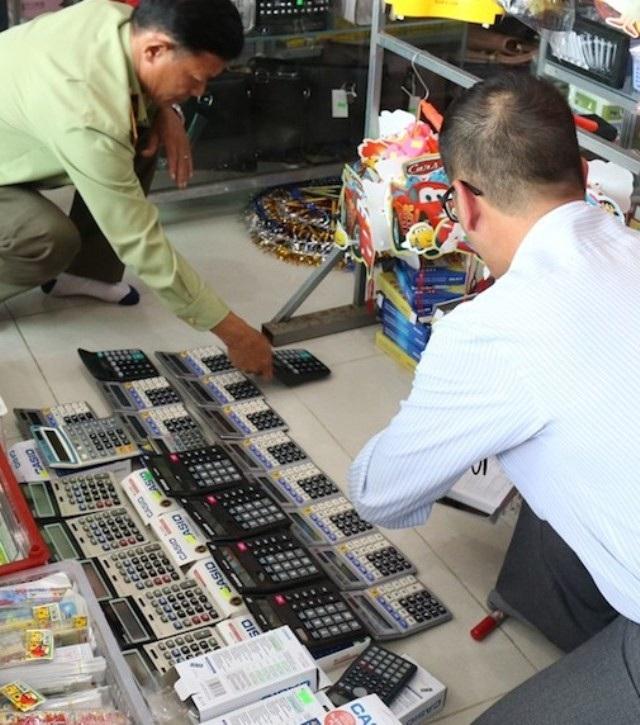 Lực lượng chức năng đang kiểm tra máy tính cầm tay có dấu hiệu làm giả nhãn hiệu. (Ảnh: CTV)