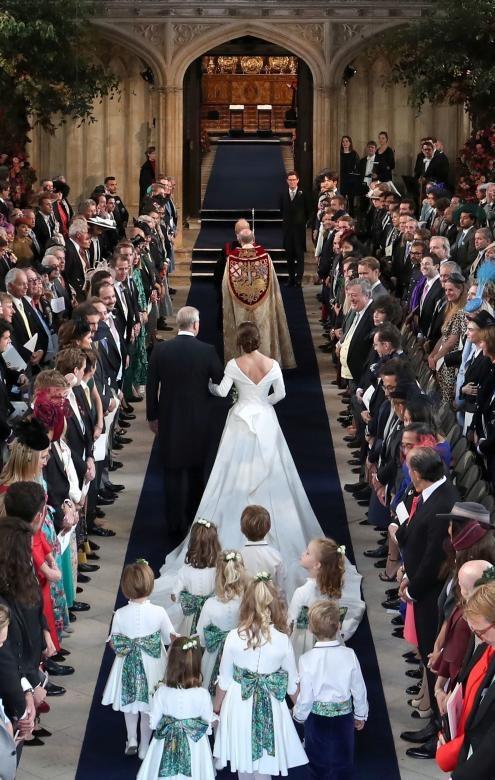 Công chúa Eugenie của xứ York là con gái của Hoàng tử Andrew, Công tước xứ York. Cha cô là con trai thứ 3 của Nữ hoàng Anh Elizabeth II và hiện tại cô xếp vị trí thứ 9 trong danh sách kế thừa ngai vàng. Cô đang là giám đốc phòng trưng bày nghệ thuật Hauser & Wirth tại London. Trong ảnh: Hoàng tử Andrew đưa con gái vào lễ đường nhà nguyện St George.