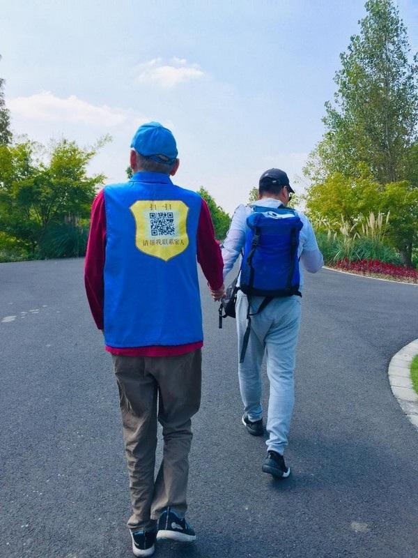 Người đàn ông mặc chiếc áo với mã QR in ở đằng sau, nắm chặt tay con mình trên đường