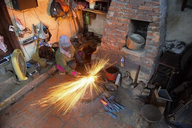 Cũng như bao nghề truyền thống của Việt Nam, nghề rèn dao kéo thủ công truyền thống ở Đa Sỹ (Hà Đông, Hà Nội) trải qua nhiều thăng trầm theo sự biến đổi của thời cuộc. Thế nhưng hơn 30 qua, bà Tuyến vẫn gắn bó với lò lửa, búa đe dù đây là công việc chuyên dành cho những người đàn ông. (Ảnh: Toàn Vũ)
