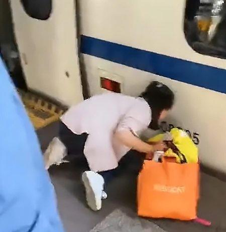 Bà mẹ hoảng sợ quỳ sụp xuống đất, mò mẫm khoảng không giữa tàu và đường ray