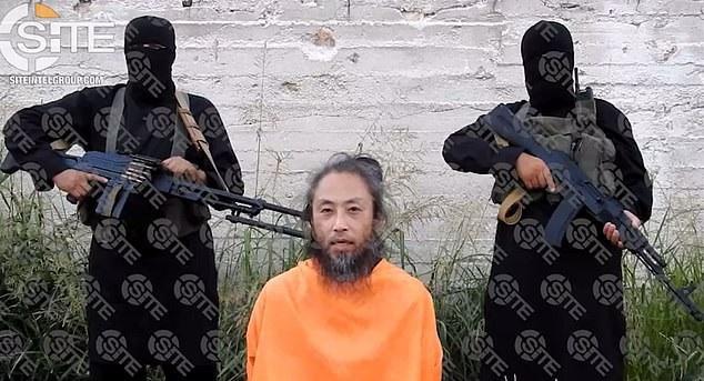 Ông Yasuda bị những kẻ bắt cóc dí súng vào đầu trong bức ảnh công bố hồi tháng 7 năm nay (Ảnh: AFP)