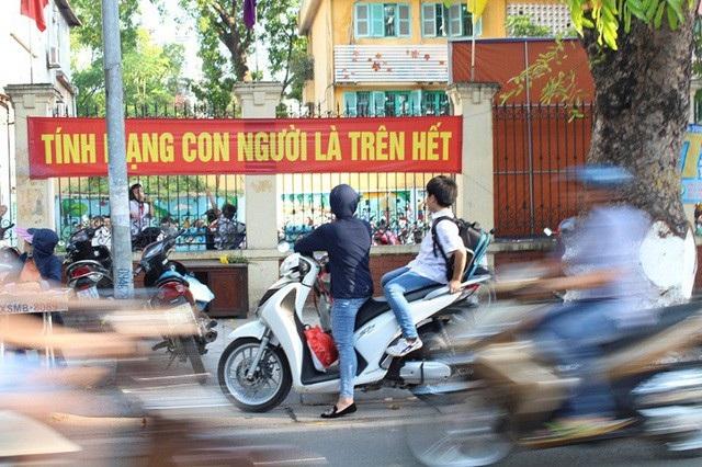 Nhiều phụ huynh bất cẩn chở con đi học không đội mũ bảo hiểm cho các cháu. Tình trạng trên diễn ra phổ biến trên địa bàn thành phố Hà Nội. (Ảnh: Quân Đỗ)