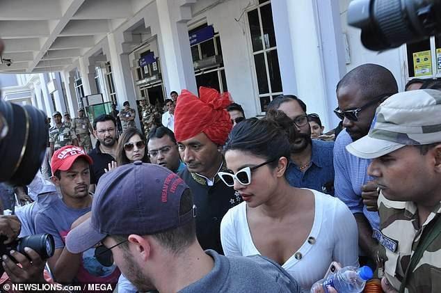 Một đám đông người hâm mộ và thợ săn ảnh đeo bám cặp đôi nổi tiếng này