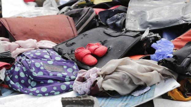 Một đôi giày trẻ em nằm ngổn ngang trên di vật của các hành khách (Ảnh: EPA)
