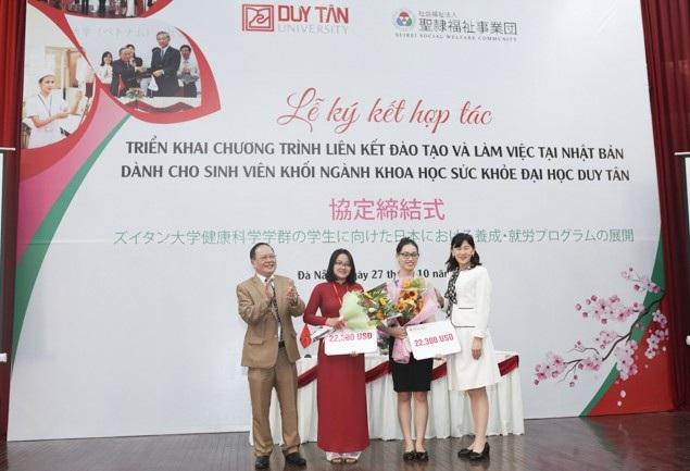 Bà Yuko Kamata - Giám đốc Điều hành Tập đoàn Phúc lợi Xã hội Seirei (ngoài cùng bên phải) trao Học bổng cho giảng viên Đoàn Nữ Nga My (áo dài đỏ) và Nguyễn Thị Lan Hương (thứ 2 từ phải sang)