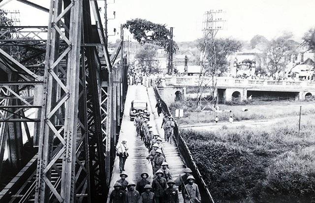 Một đơn vị Quân đội Nhân dân Việt Nam đang tiếp quản cầu Long Biên. Phía sau là các sĩ quan Pháp đang làm thủ tục bàn giao và rút khỏi Hà Nội, ngày 9/10/1954.