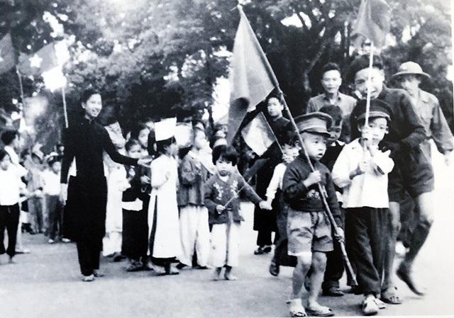 Trẻ em Hà Nội náo nức cầm cờ đi đón các chú bộ đội.