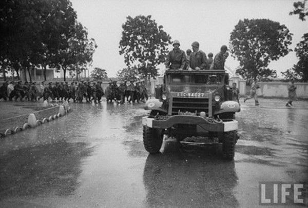 Lính Pháp trên một xe quân sự quay đầu lại nhìn đoàn quân Việt Minh đang tiến vào thành phố.