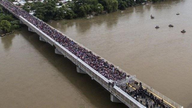 Đoàn di dân tới Mỹ chen chúc qua một cây cầu. (Ảnh: AFP)