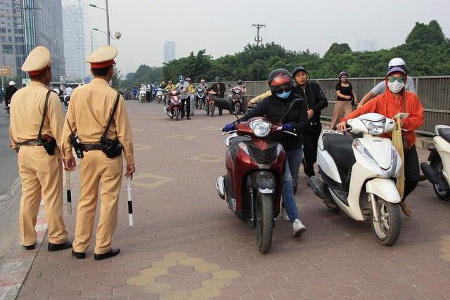 Đoàn người đi xe máy ngược chiều trên vỉa hè nút giao thông Mỗ Lao - Tố Hữu (Hà Đông, Hà Nội) lũ lượt xuống xe dắt bộ để đối phó với lực lượng CSGT làm nhiệm vụ tại đây. (Ảnh: Trần Thanh)