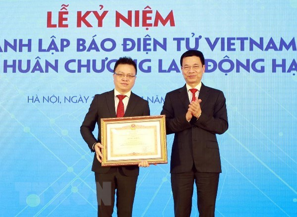 Ông Nguyễn Mạnh Hùng - Bộ trưởng Bộ Thông tin và Truyền thông (bên phải) trao bằng khen của Thủ tướng Chính phủ cho ông Lê Quốc Minh - Phó Tổng Giám đốc Thông tấn xã Việt Nam, Tổng Biên tập đầu tiên của Báo Điện tử VietnamPlus. (Ảnh: TTXVN)