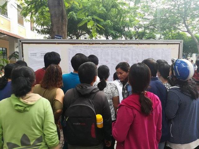 Phụ huynh tại TPHCM theo dõi danh sách của con trong đợt chạy đua vào lớp 6, Trường THPT chuyên Trần Đại Nghĩa, TPHCM.
