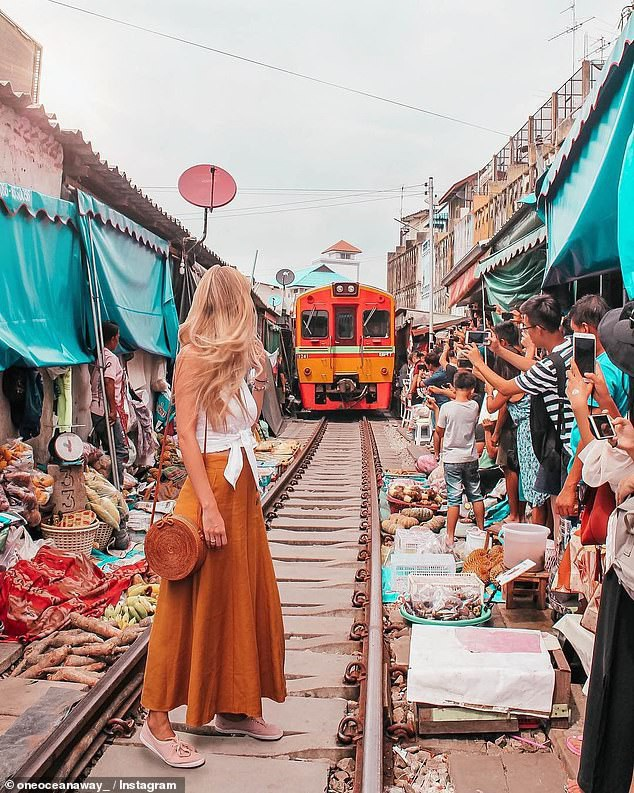 Nữ blogger đứng dưới đường ray chụp ảnh khi con tàu đang đi tới