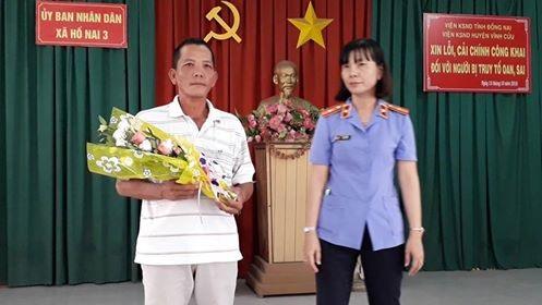 Bà Phạm Thị Mến, Viện phó Viện KSND huyện Vĩnh Cửu tặng hoa cho ông Bùi Xuân Quang tại buổi xin lỗi công khai.