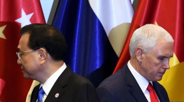 Thủ tướng Trung Quốc Lý Khắc Cường (trái) và Phó Tổng thống Mỹ Mike Pence rời sân khấu sau nghi thức chụp ảnh chung tại hội nghị ASEAN ở Singapore ngày 15/11. (Ảnh: AFP)