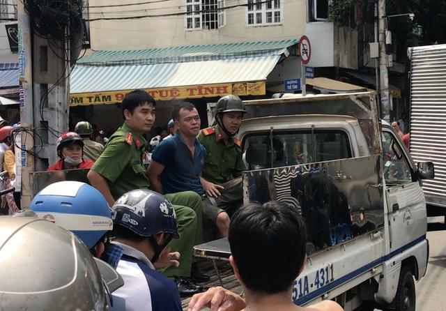 Châu Dung Thành (ngồi giữa) lúc bị công an bắt. Ảnh: Xuân Duy