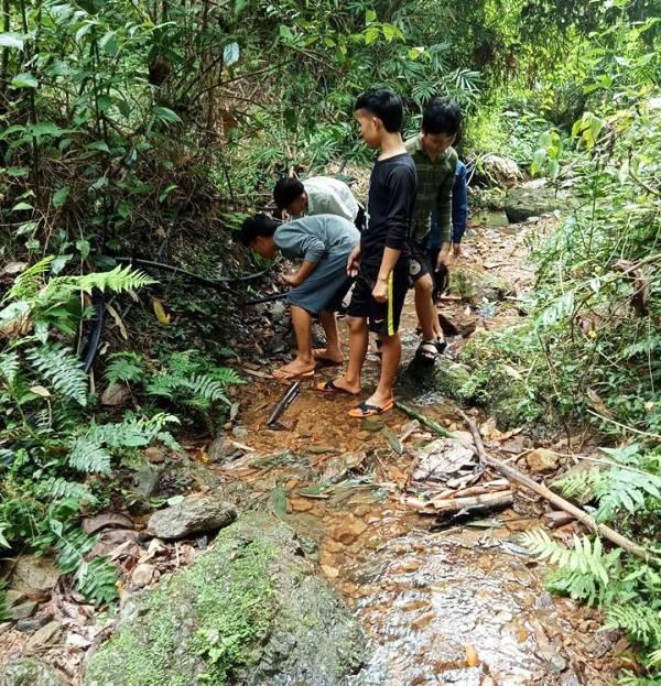 Các em học sinh đang tự tay sửa lại đường dây dẫn nước.