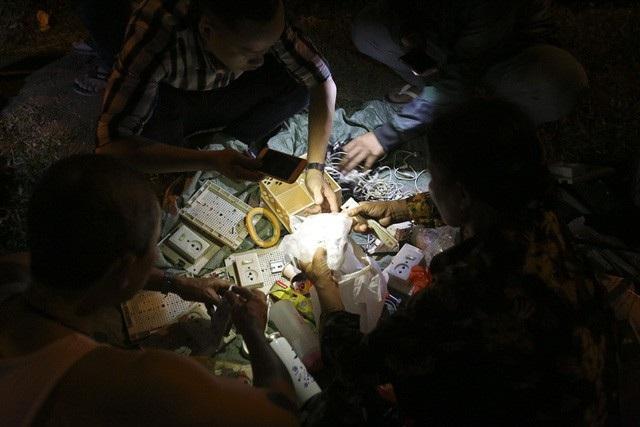 Trong không gian tối đen về đêm tại công viên hồ Đền Lừ, chợ đồ cũ diễn ra rôm rả với rất đông người mua, kẻ bán. Tất cả đều phải soi đèn để chọn hàng tạo nên cảnh chợ đặc biệt ngay giữa Thủ đô. (Ảnh: Hữu Nghị)