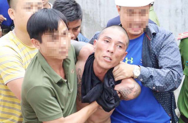 Lê Ngọc Hà bị khống chế, bắt giữ sau khi ném đứa con 2 tuổi từ mái tôn xuống đất (ảnh T.Tâm)
