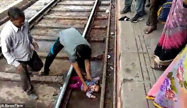 Bé gái nằm lọt thỏm giữa đường ray