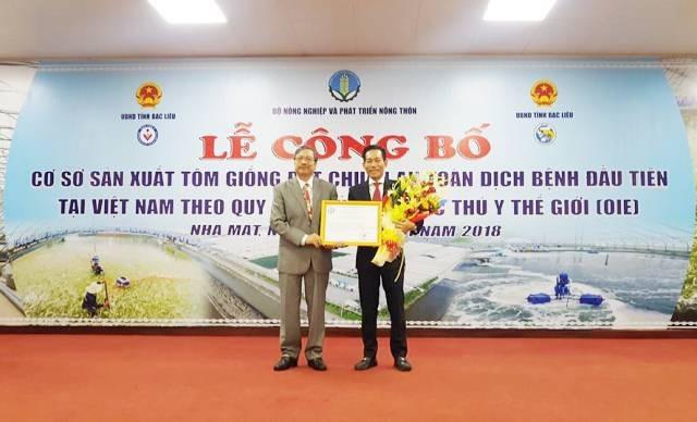 Lãnh đạo Cục Thú y (trái) trao chứng nhận cơ sở sản xuất tôm giống đạt chuẩn an toàn dịch bệnh đầu tiên tại Việt Nam theo quy định của Tổ chức Thú y thế giới cho đại diện lãnh đạo Tập đoàn Việt - Úc.