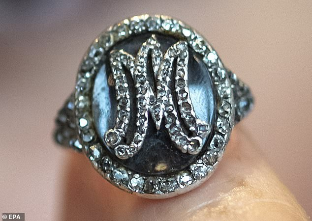 """Một chiếc nhẫn gắn kim cương với mặt nhẫn có hai chữ """"MA"""" lồng nhau là hai chữ cái đầu trong tên của hoàng hậu. Trong mặt nhẫn này có chứa những sợi tóc của hoàng hậu."""