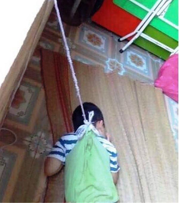 Bé P. bị buộc dây vào cổ treo lên cửa sổ khiến nhiều người bức xúc.