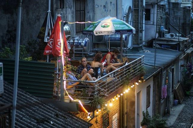 Những du khách nước ngoài ngồi đợi chuyến tàu tối lúc 19h tại một quán cà phê nhỏ ở xóm đường tàu. Ảnh: Thanh Thúy