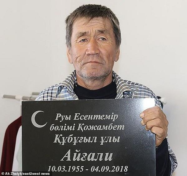 Aigali Supugaliev và tấm bia trên ngôi mộ mà người thân đã xây cho ông