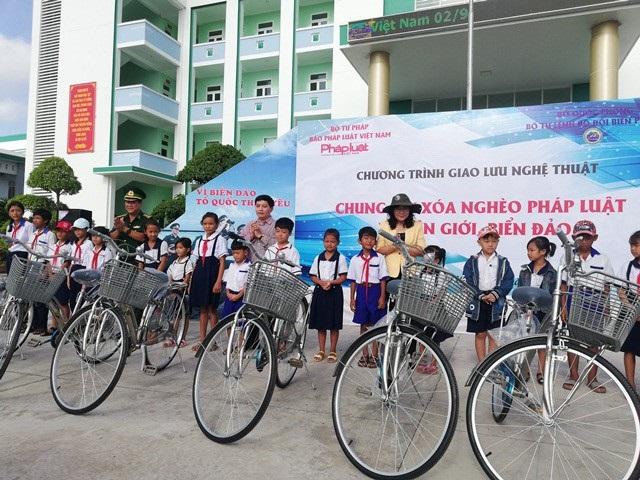 Đại diện lãnh đạo UBND tỉnh, Bộ đội Biên phòng tỉnh, Báo Pháp luật Việt Nam trao xe đạp cho các em học sinh.