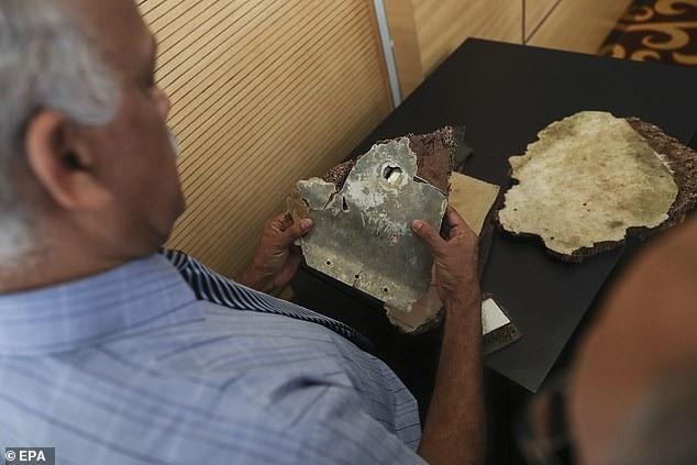 Một nhà điều tra Malaysia xem xét mảnh vỡ máy bay (Ảnh: EPA)