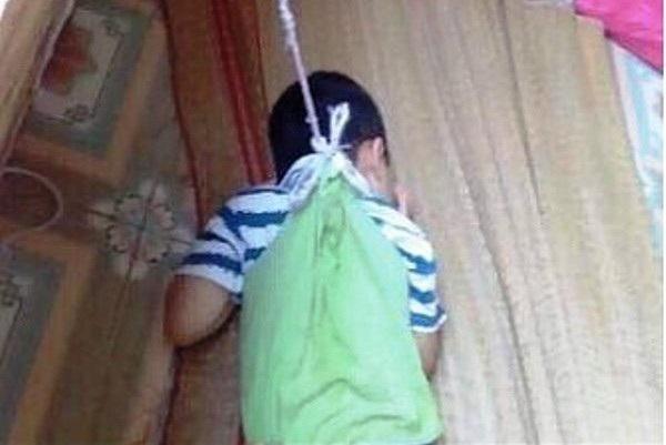 Hình ảnh cháu bé bị buộc dây treo lên cửa sổ
