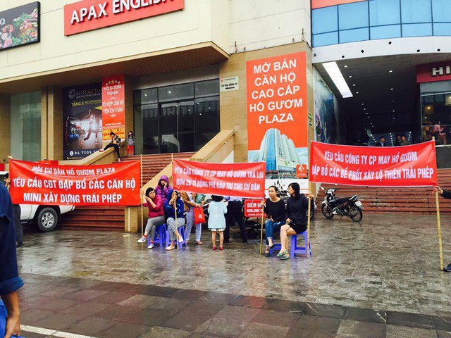 Cư dân đội mưa, giăng băng rôn trước toà nhà phản đối chủ đầu tư.