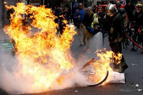 """Lính cứu hỏa vật lộn dập lửa chiếc xe đạp bị đốt cháy trong cuộc biểu tình """"Ghi-lê vàng"""" tại Paris ngày 8-12 Ảnh: REUTERS"""