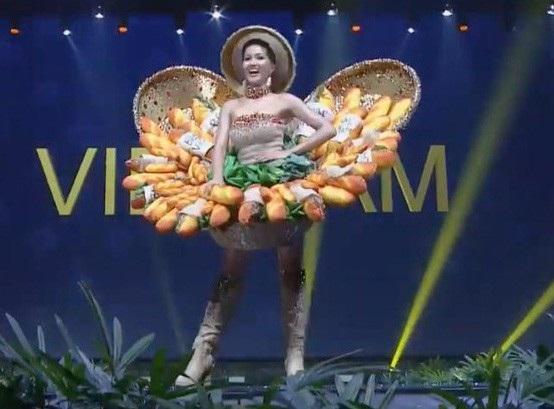 Người đẹp 26 tuổi tự tin sải bước, tay cầm một chiếc bánh mì giơ cao đầy ấn tượng. Trong phần trình diễn, đại diện Việt Nam khiến người xem thích thú khi cầm bánh mì thực hiện động tác nếm thử cùng biểu cảm đáng yêu.