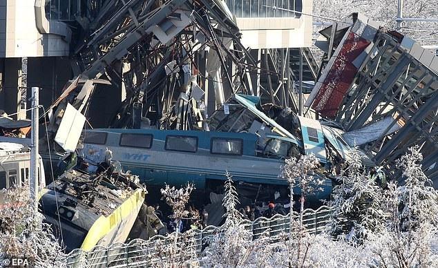 Sau vụ tai nạn, cầu vượt đã sập hoàn toàn, cách mảnh vỡ nằm la liệt trên mặt đất và các tòa tàu hư hại nghiêm trọng. Có ít nhất 2 toa tàu đã trật bánh. Các phần của cầu đi bộ kẹt chặt trên đầu đoàn tàu sau vụ va chạm cực mạnh. (Ảnh: EPA)
